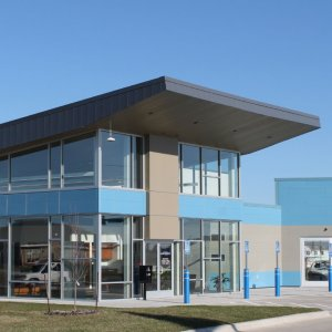 Shade Tree Auto's building exterior made with large glass walls and windows and gray and blue brick