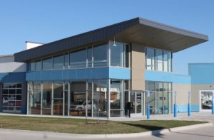 The exterior of the new Shade Tree Auto facility in Grimes, Iowa. There are floor-to-wall ceilings and blue and gray brick.