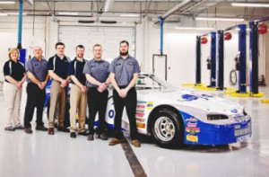 Five Shade Tree employees and owner, Clint Dudley, all pose for a photo next to the Shade Tree Auto racecar in the new facility's garage. On the far left is Pam Woodard wearing a navy blue polo and khaki pants, then a technician wearing a blue button up shirt and black pants, next Clint Dudley wearing a navy blue polo and khaki pants, after him is Dustin Klein wearing a navy blue polo and khaki pants, then two more technicians wearing blue button up shirts and black pants.