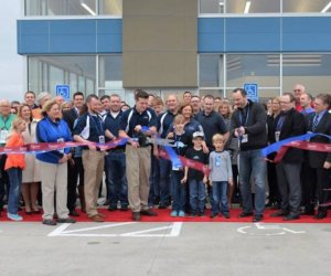 A large group of people standing on a red carpet in front of the new Shade Tree Auto building watching Clint Dudley use large black scissors to cut through a blue and red ribbon