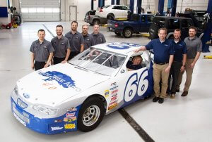 Nine Shade Tree Auto employees pose for a photo in their garage surrounding their Shade Tree Auto themed racecar. Five men are positioned to the right of the car wearing gray button up short-sleeved shirts and black pants, two men and Clint Dudley are wearing khaki and black pants with blue and gray Shade Tree Auto polos standing on the left side of the car, and a woman is smiling in the drivers seat.