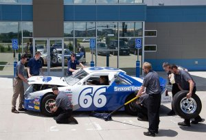 Nine Shade Tree Auto employees perform a pit stop on a Shade Tree Auto themed racecar with the number 66 on the side in front of the Shade Tree Auto building. One man is pouring gas in the tank, one man is carrying a tire to the back of the car, one man is adjusting the back left wheel, one man is raising the car, one man is adjusting the front left wheel, Clint Dudley is lifting up the front hood of the car, one man is looking at Clint, one is using a towel to clean off the front windshield and a woman is sitting in the drivers seat.