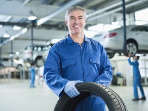A middle-aged man with gray hear is wearing a blue jumpsuit, white undershirt, and blue plastic gloves as he holds a large black rubber tire. Behind him are four silver cars on blue jacks with auto technicians working on each one.