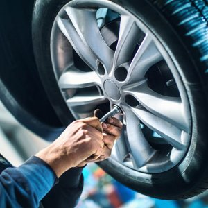 Closeup of an auto technician's hand unscrewing the bolts on a rim of a car in order to replace the tire. The car is lifted up on a jack and the mechanic is wearing a blue jumpsuit.