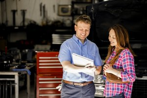 An auto mechanic with a white binder and black pen discusses auto repairs with a latin woman wearing a red and purple plaid shirt and holding a brown leather purse. They are standing in front of an auto repair garage with a large red tool box, metal equipment, and a black SUV positioned behind them.